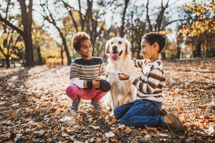 Golden Retriever sitting with two children outside in park